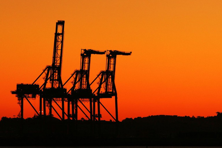 The Port of Oakland's container cranes at sunset