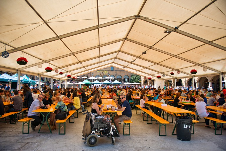 Bavarian styled Oktoberfest in Barcelona, Spain taking place in an undercover marquis with rows of benches and people © PlusONE / Shutterstock