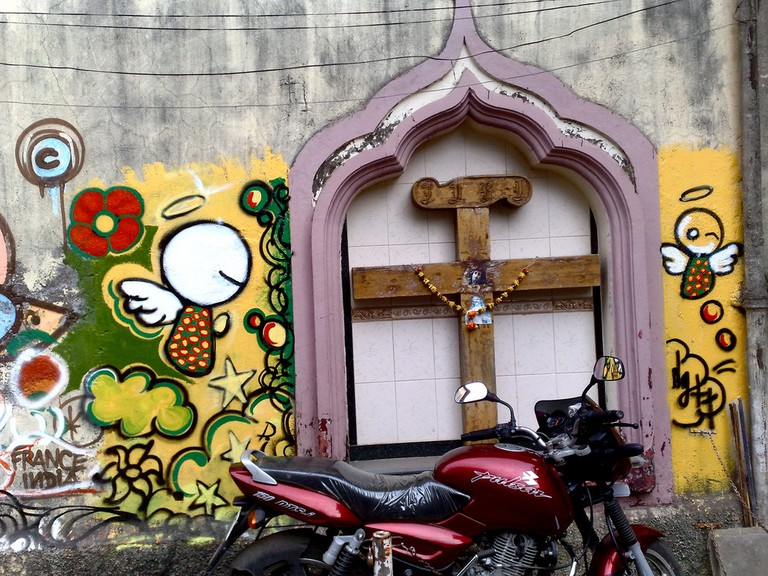 A typical bandra corner housing a cross contrasted with fresh graffiti