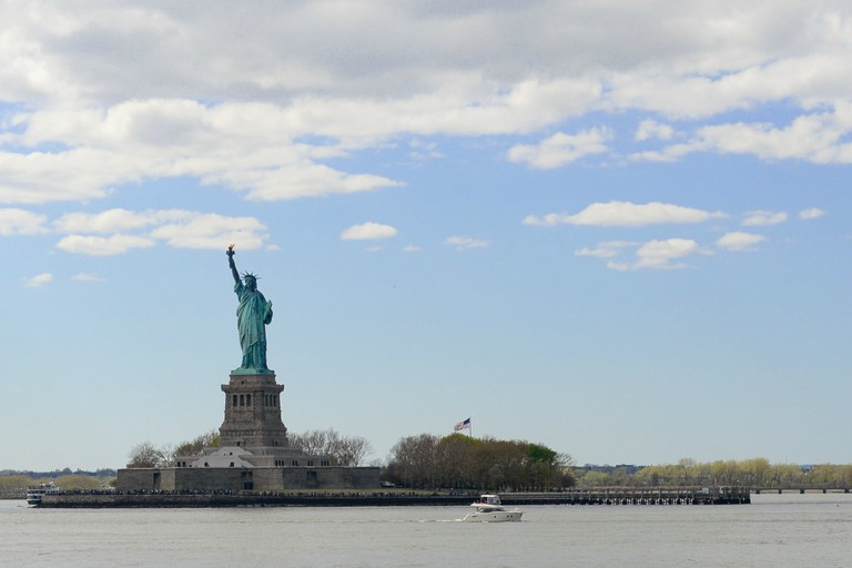 A small boat travels by the Statue of Liberty | © Smart Scott Photography
