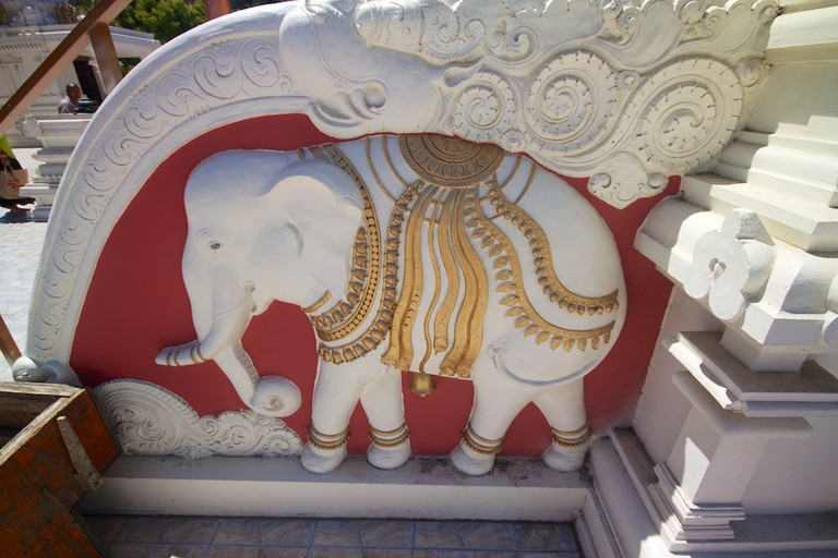 An elephant sculpted onto a small stairway at the temple is a symbol of spiritual strength