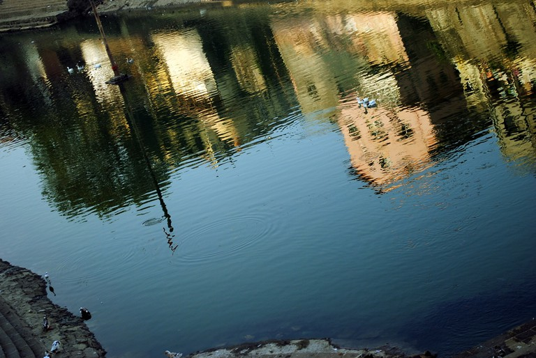 A reflection of the surrounding structures in the calm waters of Banganga | ©Neehar Mishra