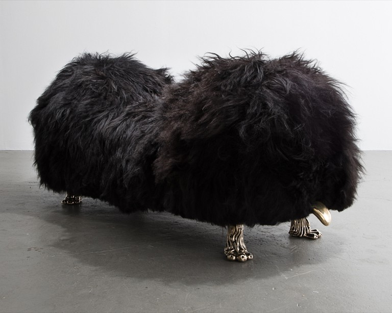 The Haas Brothers Unique Hair Witch Project mellow-hump bench with black Icelandic sheepskin and cast bronze tongue and coyote feet