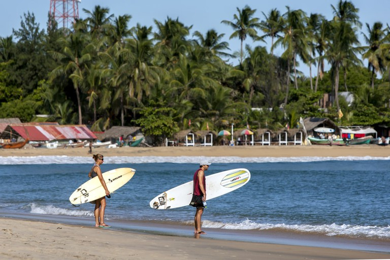 A pair of surfers look towards the point break waves at Arugam Bay in Sri Lanka