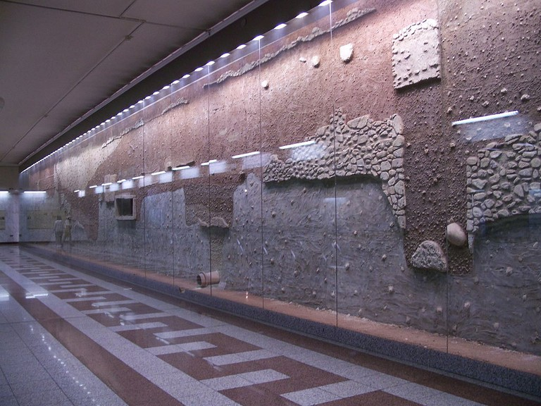 Stratigraphy of the antiquities wall of the Athens Metro Syntagma station, with the pipe in the center belonging to the Peisistratid Aqueduct.