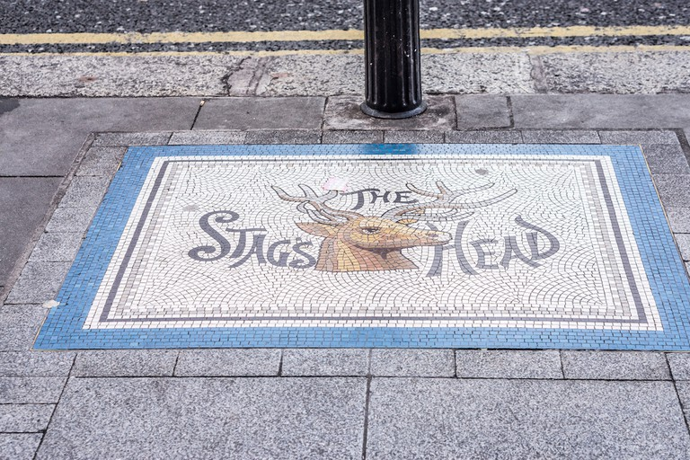 A pavement mosaic points the way to The Stag's Head pub