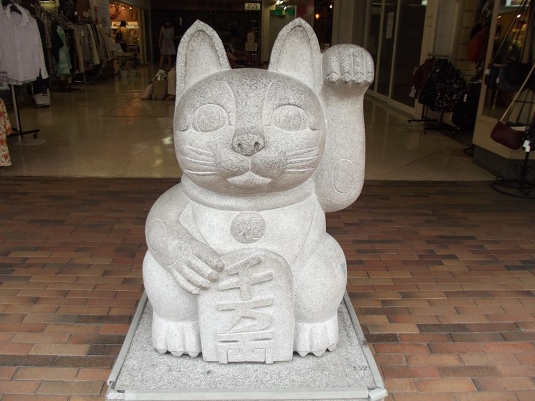 A Japanese maneki neko statue beckons customers outside of a store