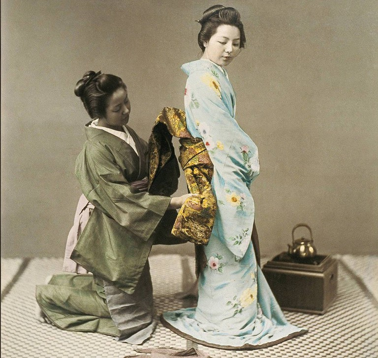 A geisha gets help with her obi   © The Burns Archive/WikiCommons