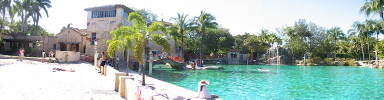 Panoramic shot of the pool, its historic lookout towers, and majestic falls