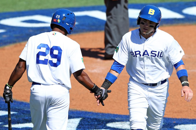 Dante Bichette Jr. is greeted by teammate Juan Carlos Muniz (29) after scoring a run during Game 1 of the 2016 WBC Qualifier
