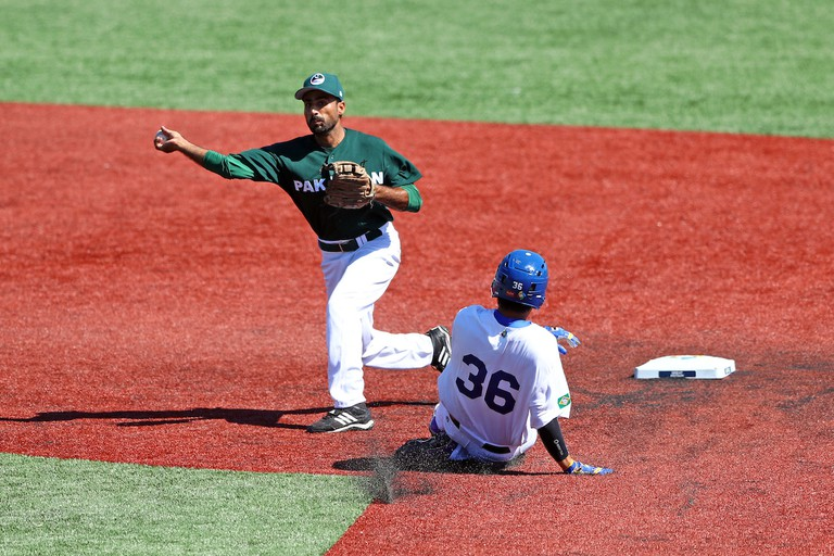 Faquir Hussain of Pakistan turns a double play as Brazil's Reinaldo Sato (36) slides into second base