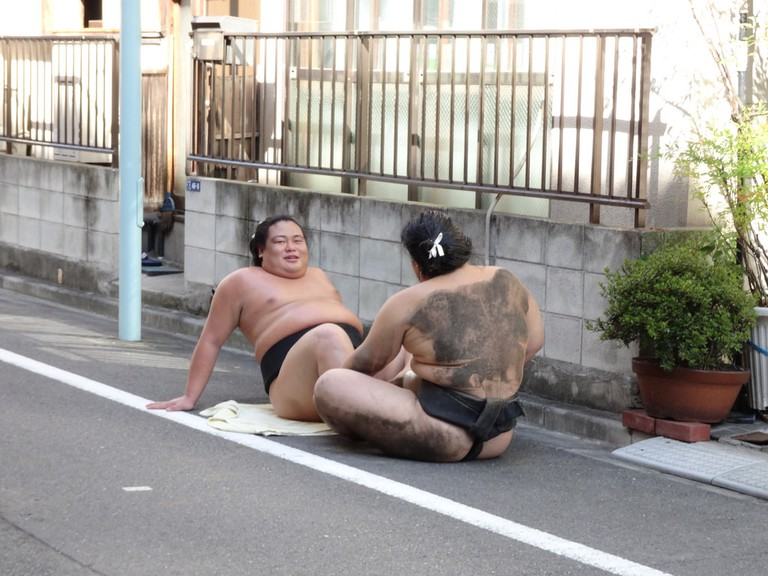 Wrestlers from Arashio Sumo Training Stable (Heya) doing situps in the street
