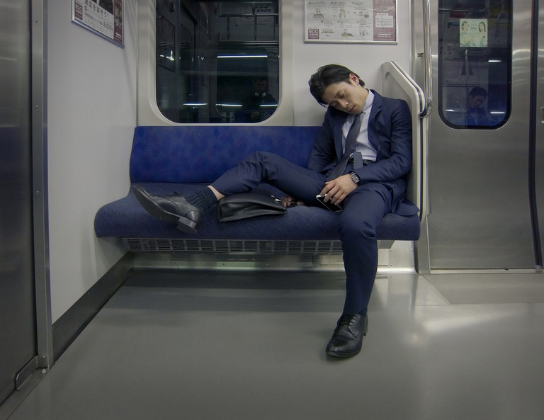 Salaryman asleep on the subway