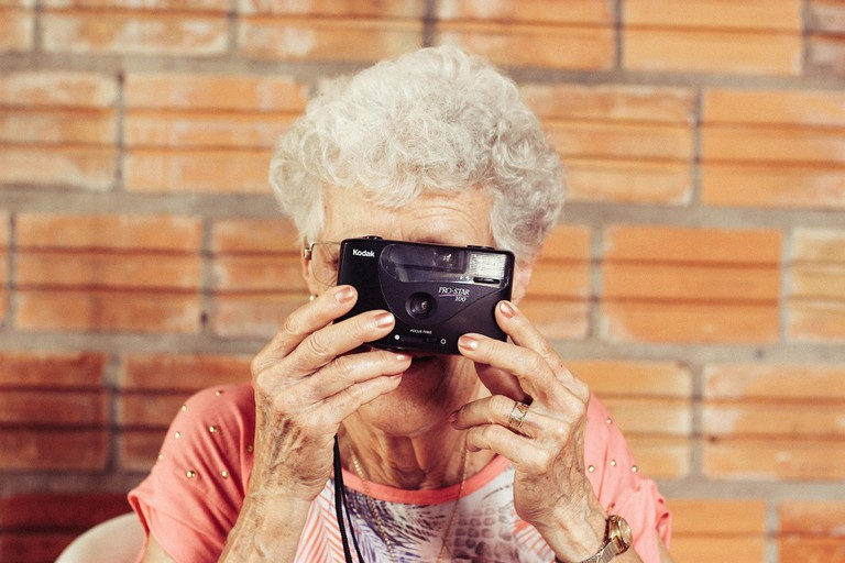 An elderly woman poses with her camera | © Tiago Muraro/Unsplash