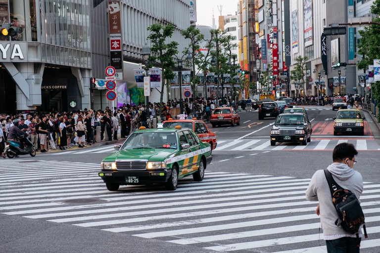 Cars drive through Shibuya Crossing.
