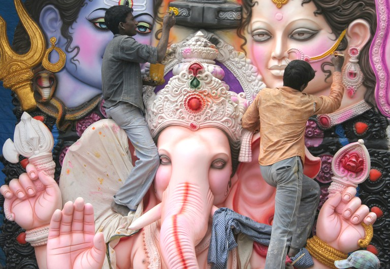 Artists working on a giant statue of Ganesha