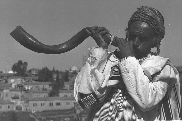 Jewish man blowing a shofar on Rosh Hashanah