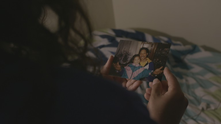Aja Carter looks at an old photo of her and her father | © Drew English