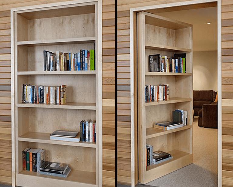 Hidden bookcase door by DeForest Architects