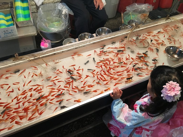 A little girl in yukata prepares for a round of goldfish scooping