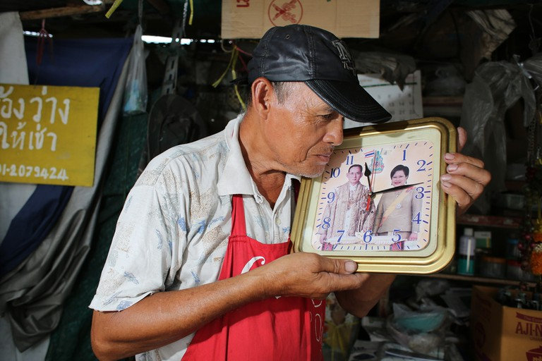 Thai man showing picture of King Bhumibol and Queen Sirikit