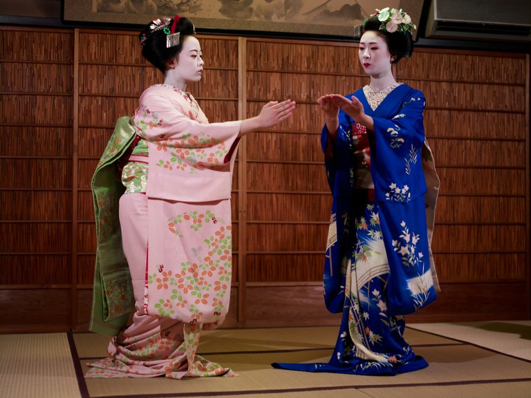 Geishas performing a dance dressed in kimonos