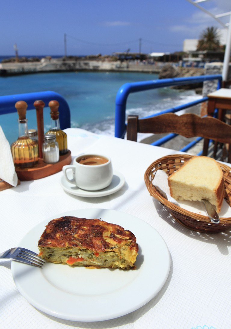 A vegetarian meal of traditional Cretan boureki (courgette, carrot and other vegetables with mizythra cream cheese, topped with grated cheese and baked), bread and coffee at a taverna in Chora Sfakion