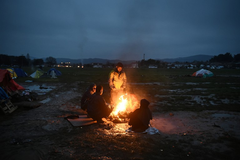 Stranded refugees try to warm up around a fire, in the makeshift camp at the northern Greek village of Idomeni at the Greek-Macedonian border