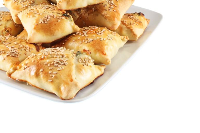 Cretan pies kalitsounia with cheese, herbs and sesame seeds