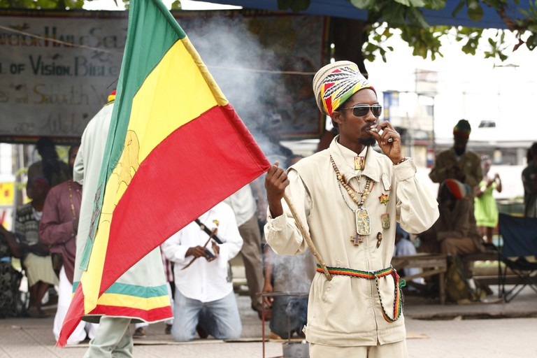 Flag wavers for the outdoor worship service of a Rasta community