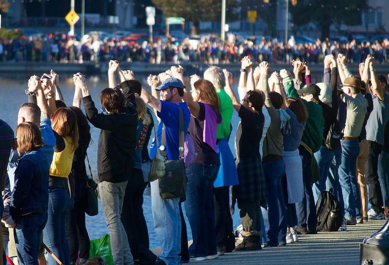 """Hands Around Lake Merritt"" – A recent peaceful protest in Oakland © Noah Salzman/Wikipedia"