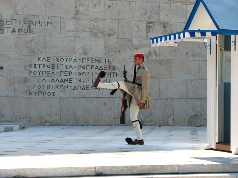 An evzone lifts his leg up to shoulder height