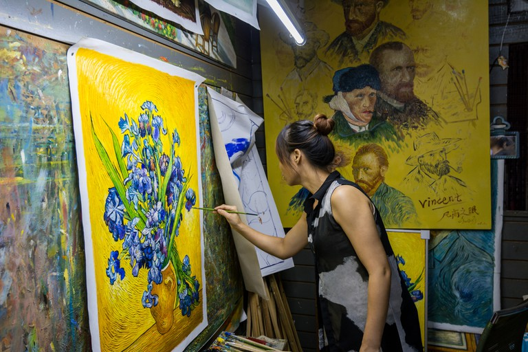 A female painter painting a Vincent van Gogh masterpice in her studio in Dafen