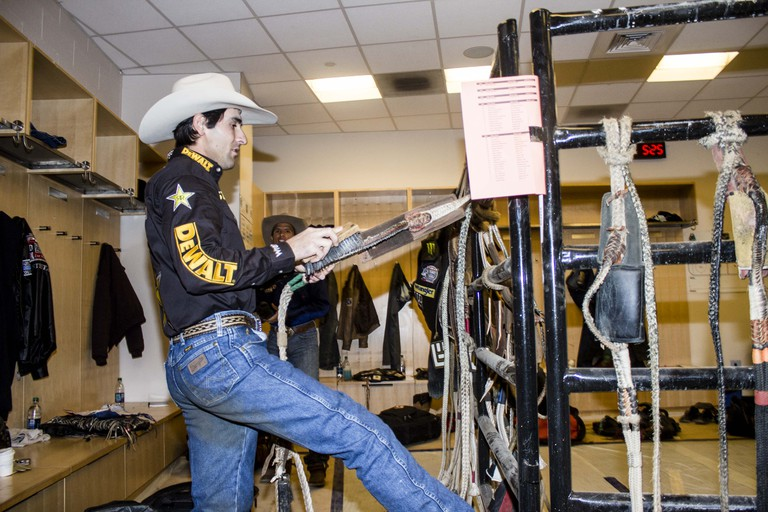 Silvano Alves readies his rope in the locker room before riding.   © Amanda Suarez