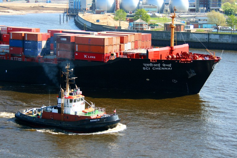 A container ship being guided out of the Hamburg port