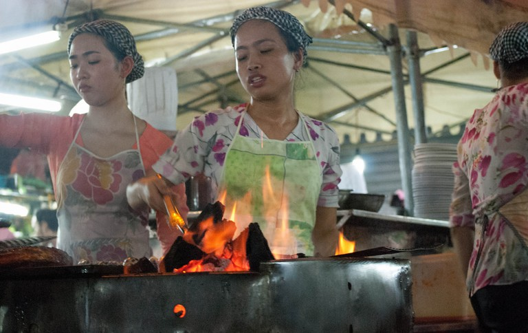 Vietnamese cooks in a steaming-hot street food marquee