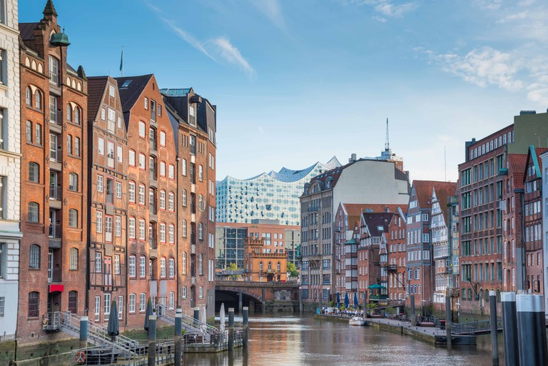 scenic view of historic buildings on both sides of Nikolaifleet channel in Hamburg, Germany with Elbphilharmonie concert hall in background under beau