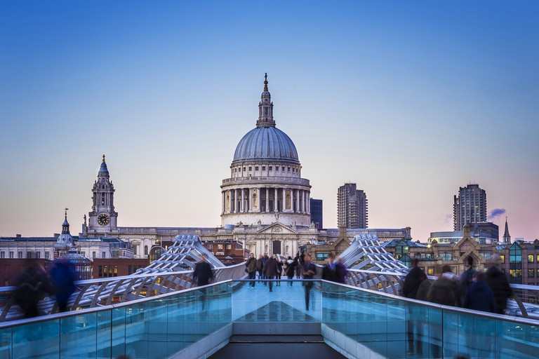 Londoners walking through Millennium Bridge with St.Paul's Cathedral at the background after sunset - London, UK |© Zoltan Gabor/Shutterstock