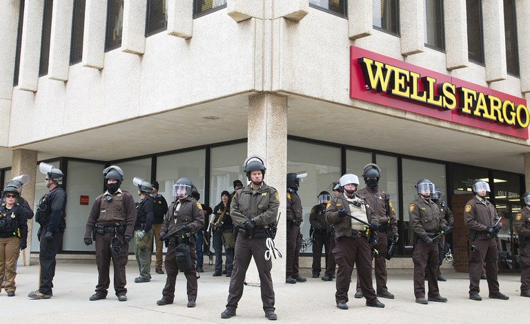 Police in riot gear guard a bank in Bismarck, North Dakota
