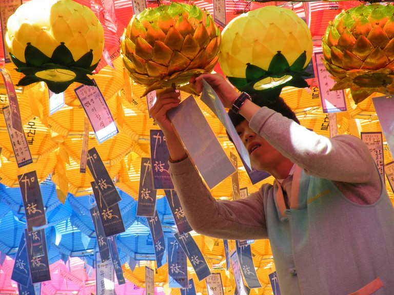 A temple-goer hangs his wish on a lantern at Jogyesa Temple in Seoul