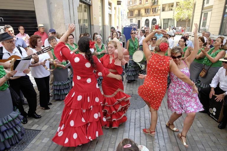 "Women wear beautiful ""trajes de gitana"" – gypsy dresses – at Málaga feria"