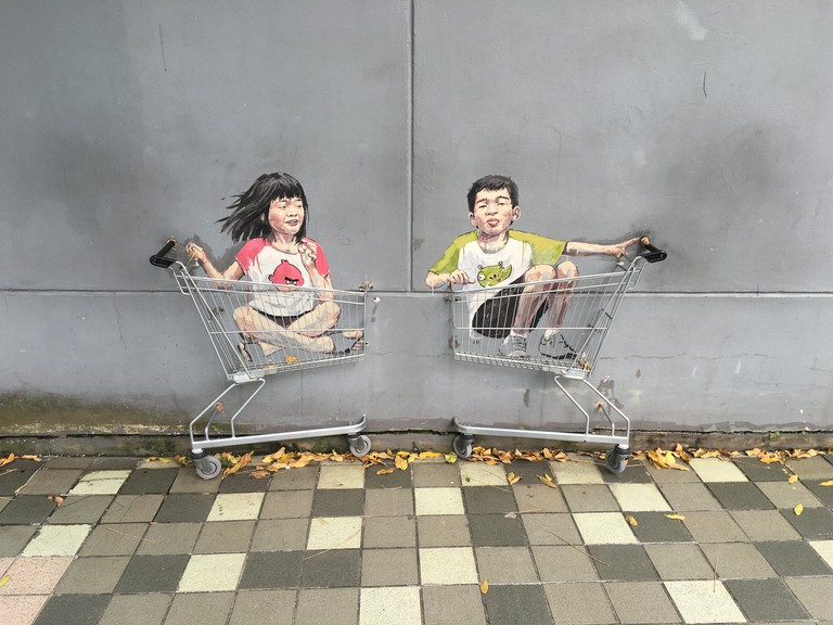 Children in shopping cart street art by Ernest Zacharevic in Singapore