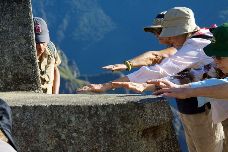 Tourists place their hands as close as possible to the Intihuata rock to channel energies.
