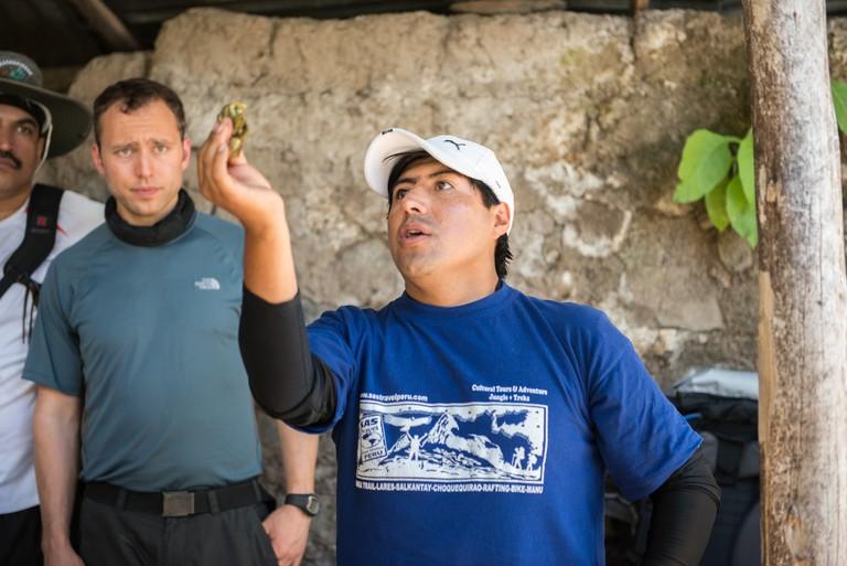 Peruvian tour guide explaining coca leaves