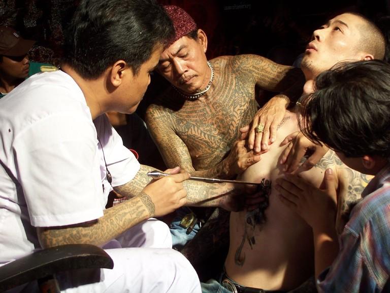 A man receiving a tattoo at a Thailand tattoo festival