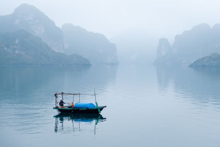 Fishing boat in the mists of Halong Bay, Vietnam