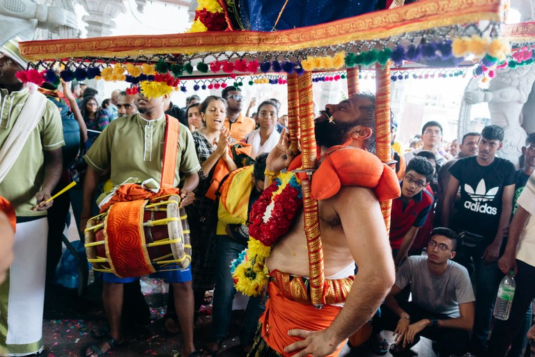 A Kavadi bearer accompanied by drums and music