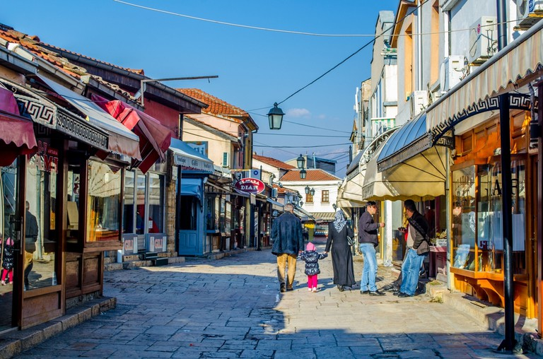 People are walking through the old town of skopje which consist of many narrow streets full of shops, restaurants and even marketplaces