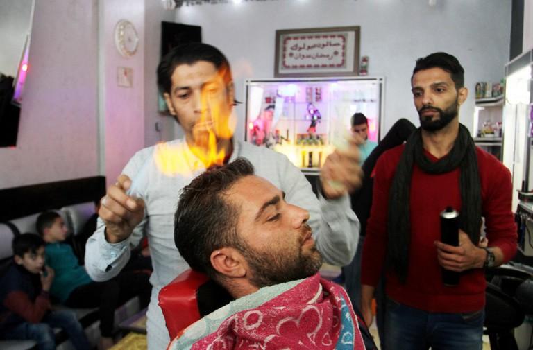 Edwan, straightening a client's hair   © APAImages / REX / Shutterstock