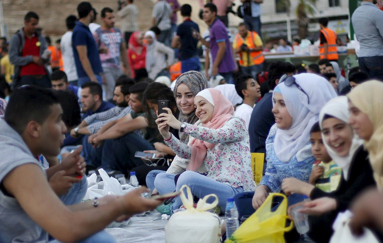 """Women take a """"selfie"""" as people gather to eat their Iftar (breaking of fast) during a local initiative called """"Let's Have Iftar Together"""" during the holy fasting month of Ramadan in Amman, Jordan June 27, 2015. © Muhammad Hamed, Reuters"""